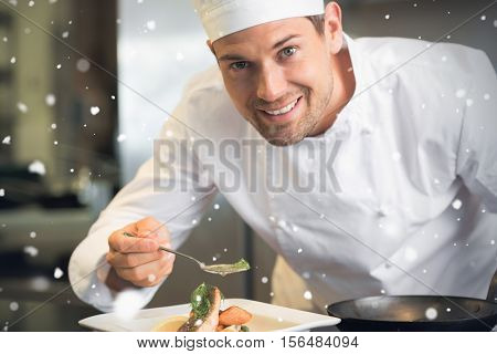 Snow falling against smiling male chef garnishing food in kitchen