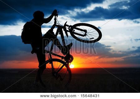 Man doing bicycle juggle on sunset background