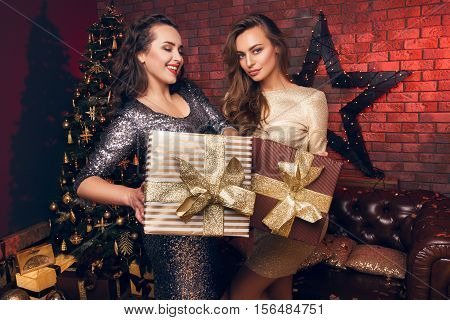 Two girlfriends with a presents. Waiting for a Christmas time. Hew Year's party. Happy Hew Year 2017.