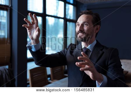 Technological achievements. Positive pleasant good looking man touching an imaginary sensory screen and smiling while standing in the conference room