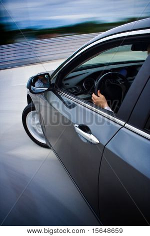 Car driving fast with blurry background.