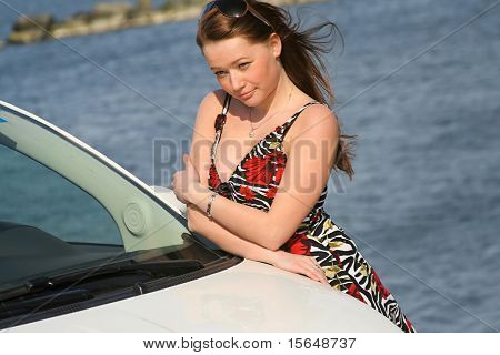 beautiful girl standing next to the car