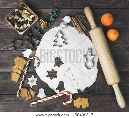 Cooking Christmas cookies. On dark brown background dough for cookies. Forms for Christmas cookies. Ingredients for Christmas cookies. Ready-baked cookies. Christmas New Year card.
