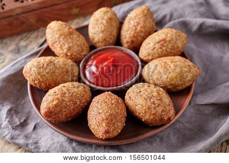 Kibbeh traditional middle eastern oriental restaurant lamb goat or camel meat stuffed bulgur kofta spicy meatball croquettes food on vintage wooden table background