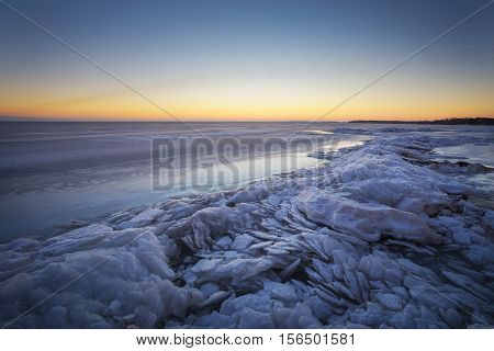Winter landscape with lake and sunset sky. Composition of nature.