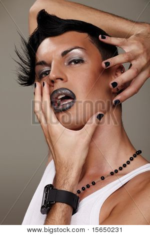 Closeup portrait of a male model with makeup isolated on grey background