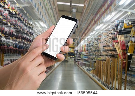human hand hold smartphone tablet cell phone with blurry hardware store. concept of shopping and finding hardware tool for house repair.