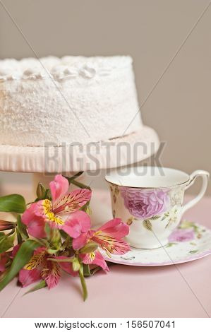 cake with whipped cream on a stand and and vivid bright pink flowers, tea accessories in the background