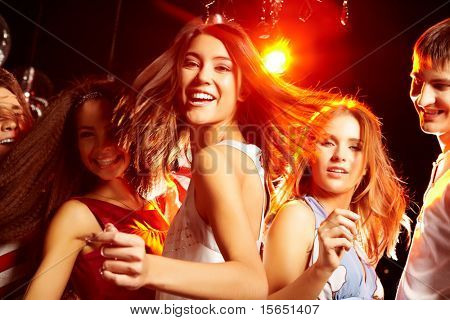 Pretty clubber dancing surrounded by her friends and looking at camera with smile