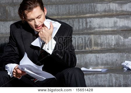 Portrait of thoughtful business man touching his chin and looking at paper