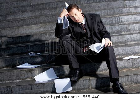 Portrait of sad businessman sitting on stairs with papers in hands and lost expression on his face