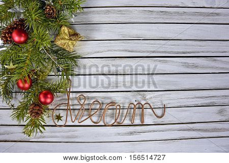 Christmas ornaments in pine bough with word dream in copper wire on rustic gray wood