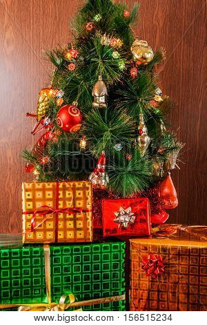 Christmas tree with gifts on wooden background