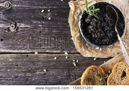 Black Astrakhan Russian salted sturgeon caviar in a can on a dark background with a wooden spoon and slices of bread. Snacks and luxury holidays. selective focus