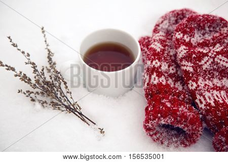 pair of red mittens lie on the snow and standing next to a mug of hot tea