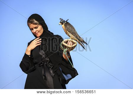 A woman in abaya with Peregrine Falcon in Dubai Desert Conservation Reserve, UAE