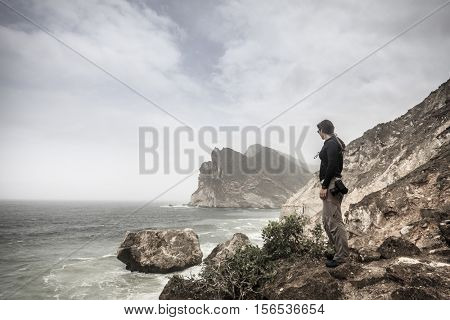 Woman photographer watching the sea from a cliff on Oman coast