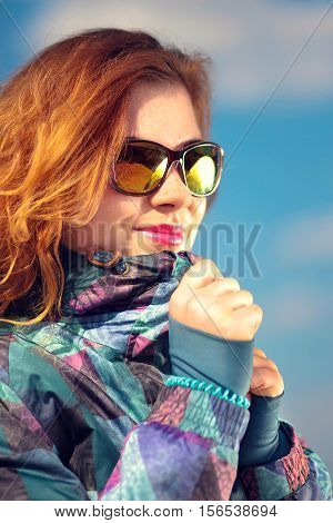 girl in a ski jacket and stylish glasses against the sky