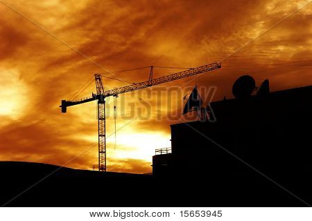 Silhouette of crane and satellite dish