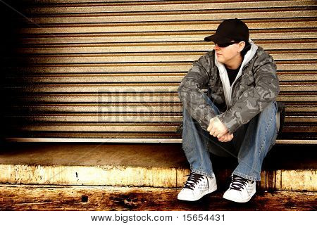 Skater sitting down on a ledge with a grunge style background