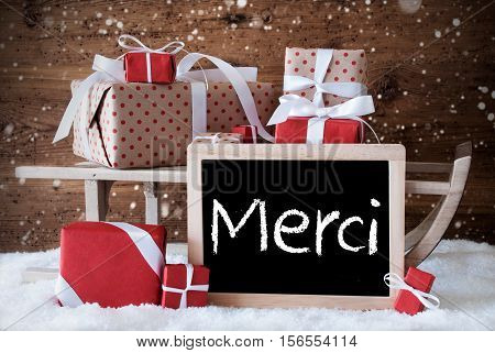 Chalkboard With French Text Merci Means Thank You. Sled With Christmas And Winter Decoration And Snowflakes. Gifts And Presents On Snow With Wooden Background.