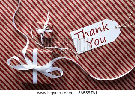 Two Gifts Or Presents With White Ribbon. Red And Brown Striped Wrapping Paper. Christmas Or Greeting Card. Label With English Text Thank You