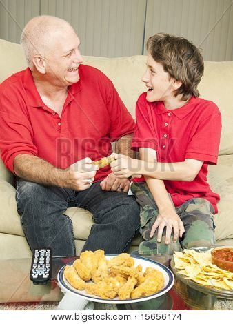 Father and son playfully fighting over a chicken wing as they watch the football game.