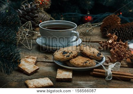 Beautiful Concept. Chocolate Cookies On A White Plate On A Wooden Background. Nearby Stands A Christ