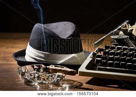 Old manual typewriter cigar and hat on wooden table
