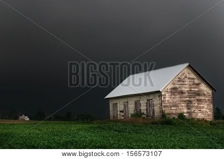 Black stormy sky in the countryside, focus on building, long exposure, some motion blur on plants