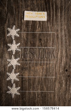 Empty list of New Year resolutions on vintage wooden background