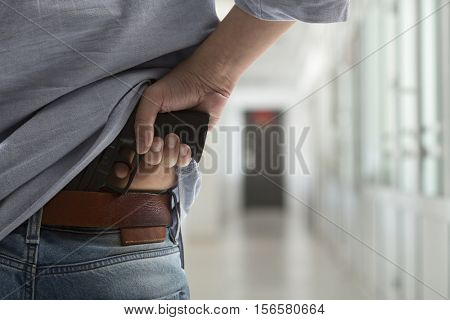 People criminal concept -  killer with a gun in the hallway