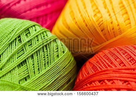 Colorful knitting thread texture, handiwork backdrop. Bright handiwork background, crochet iris green, yellow, orange and pink string, Leisure, hobby, needlework concept
