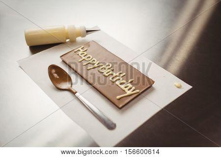 Happy birthday written on chocolate plaque in kitchen