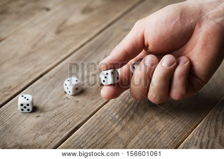 Man hand throwing white dice on wooden table. Gambling devices. Game of chance concept.