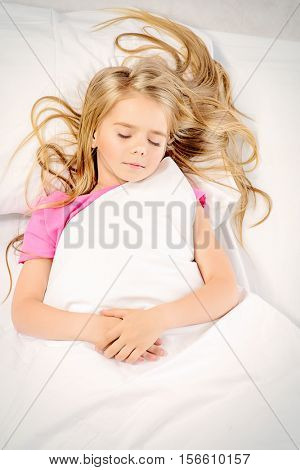 Cute little girl sleeping in her bed in the nursery. Healthcare, beauty. Sweet dreams.