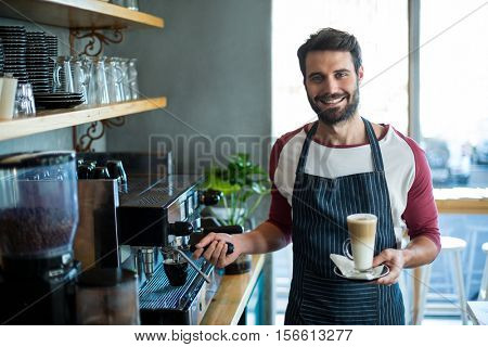 Portrait of smiling waiter holding cup of cold coffee at counter in cafe