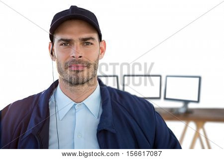 Portrait of security officer listening to earpiece with computers in background