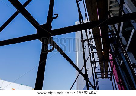 Silhouetted industrial shot node of scaffold against blue sky.