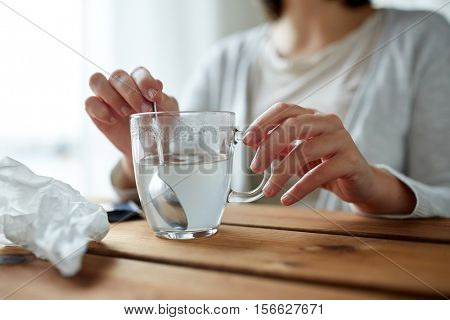 healthcare, medicine and people concept - close up of woman stirring medication in cup with spoon