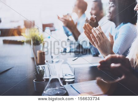 Photo of young business partners applauding to reporter after listening report at seminar. Professional education, work meeting, presentation or coaching concept.Horizontal, blurred background