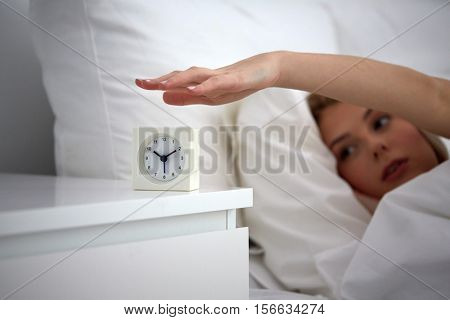 rest, sleeping, time and people concept - close up of young woman switching off alarm clock in bed at home bedroom