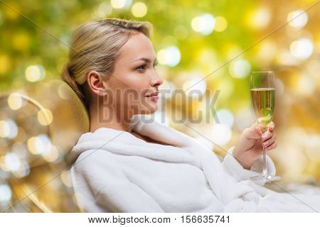 people and relaxation concept - beautiful young woman in white bath robe lying on chaise-longue and drinking champagne at spa over holidays lights background