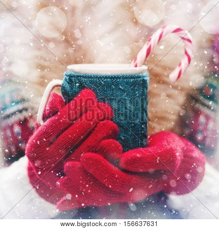 Woman holds a winter cup close up. Woman hands in woolen red gloves holding a cozy mug with hot cocoa, tea or coffee and a candy cane. Winter and Christmas time concept.