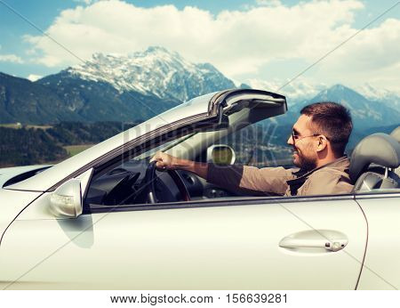 travel, tourism, road trip, transport and people concept - happy man driving cabriolet car over mountains background