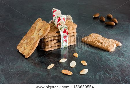 Closeup of a stack of spiced biscuits with almonds ( Spekulatius ) decorated with Christmas Bow surrounded by almonds on black background.