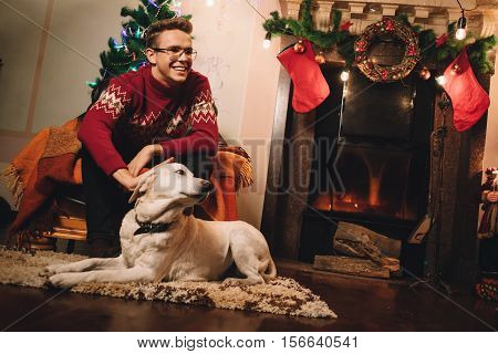 Happy man in red sweater sitting in front of the fireplace and petting pet. Smiling guy on the background of Christmas tree and chimney with his dog. Lots of scenery for the new year.