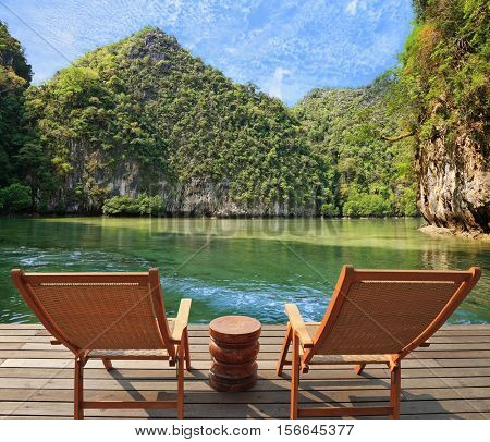 Calm beautiful landscape. Enclosed bay with clear water surrounded by green hills. The comfortable place to enjoy the beauty of the landscape. Two wooden chairs - on a wooden platform.