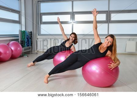 Fitness, sport, exercising lifestyle - Group of women doing exercises with fit balls in a Pilates class at the gym.