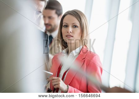 Portrait of confident businesswoman standing with colleagues in brightly lit convention center